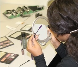 "A workshop participant of our Crisis Intervention for Child Victims of Sexual Abuse program tries out beauty products donated by Arbonne Charitable Foundation at our ""pampering day"" in October 2014."