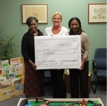 Jenny Childs (c) from Arbonne Charitable Foundation presents a check to PEI Kids' Executive Director, Roz Dashiell, (l) and Clinical Director, Dr. Juanita Brooks (r) in November 2014.