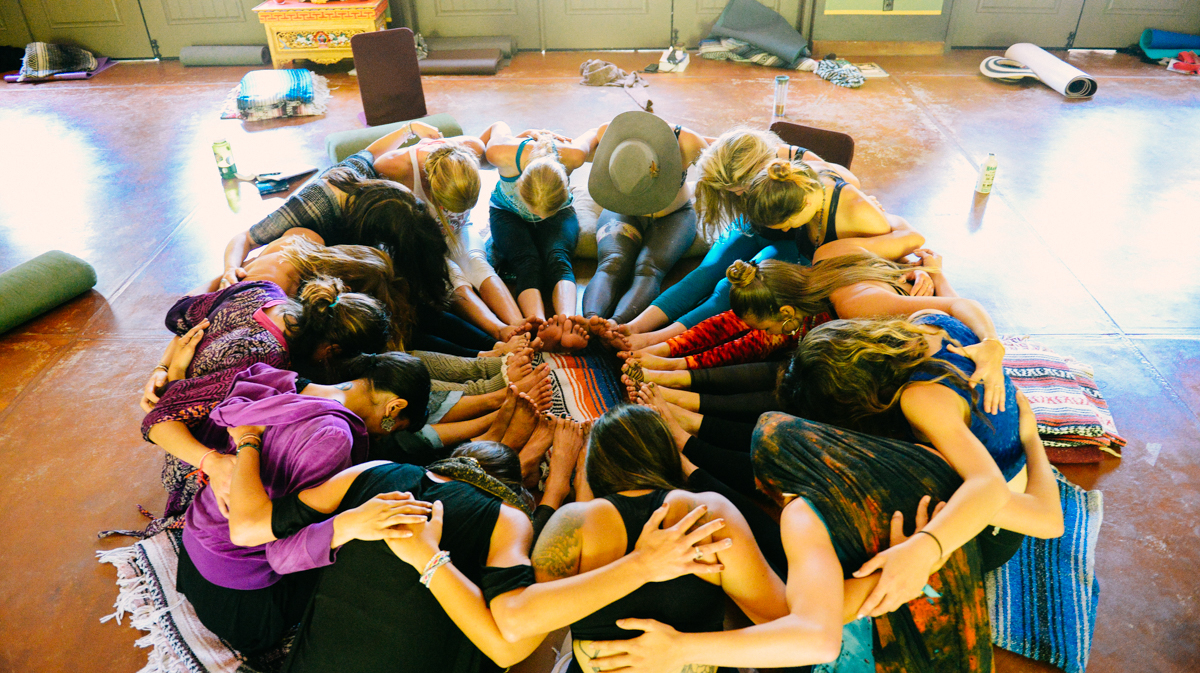 Group of people huddled in a circle on the floor