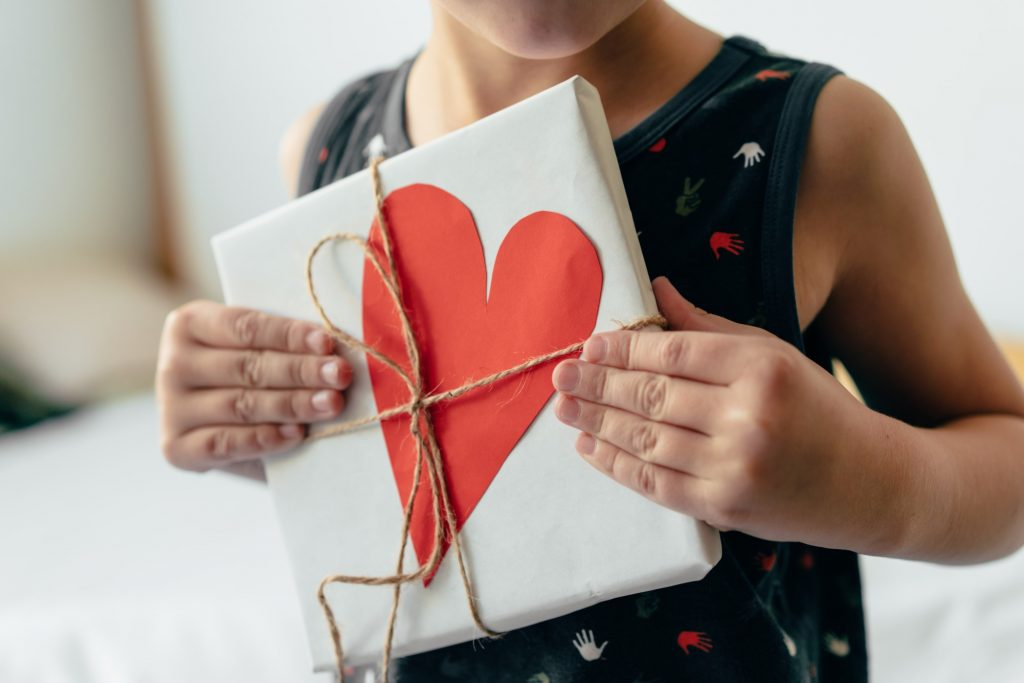 Young boy holding a gift wrapped in a box with a heart