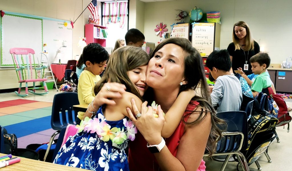 Little girl hugging her kindergarten teacher in class
