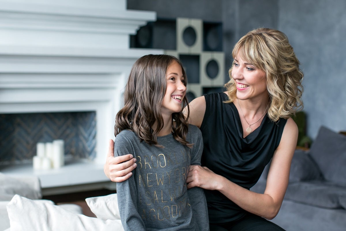 A mother and daughter smiling at each other in a living room
