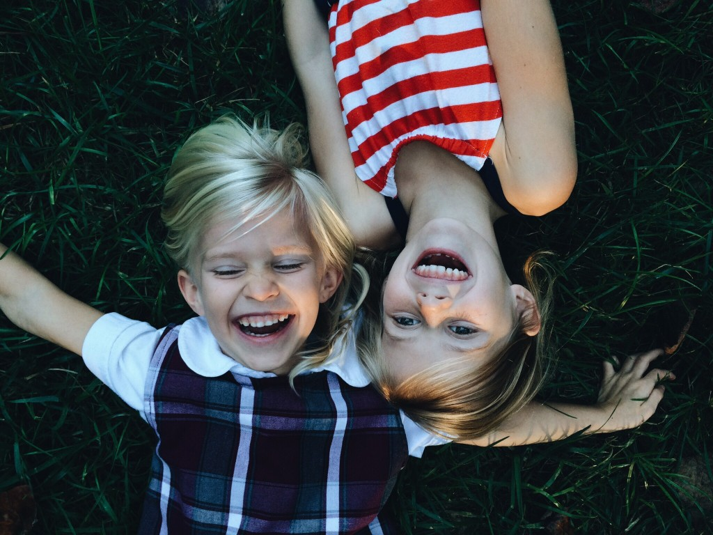 Two young children lying on the ground outside and having fun