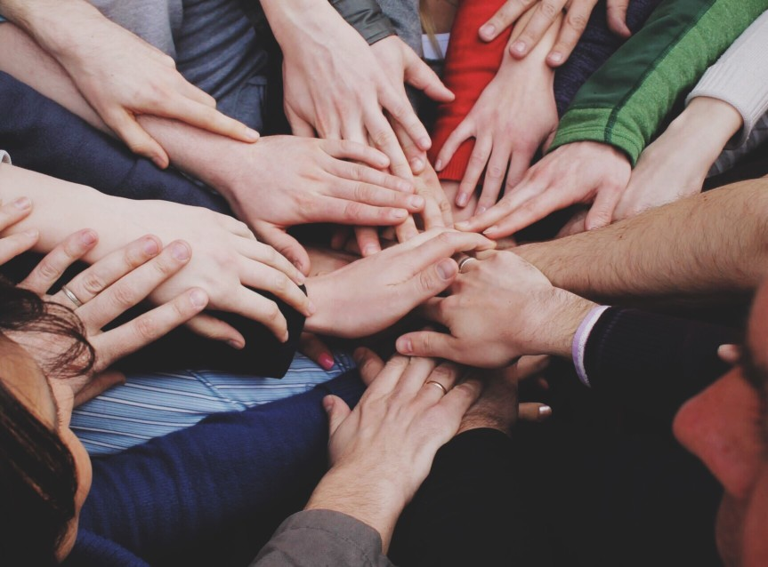 Team of people putting their hands in a circle